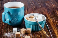一个蓝色陶瓷杯子用茶和有藤茎和白糖的一个糖罐的特写镜头在一张木桌上 图库摄影