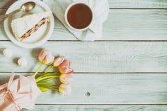 一个蛋糕用樱桃、茶和在白色木桌上的桃红色郁金香 库存图片