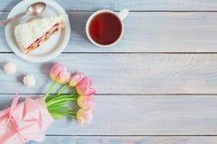 一个蛋糕用樱桃、茶和在白色木桌上的桃红色郁金香 免版税库存图片