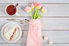 一个蛋糕用樱桃、茶和在白色木桌上的桃红色郁金香 图库摄影