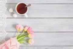 一个蛋糕用樱桃、茶和在白色木的桃红色郁金香 库存图片
