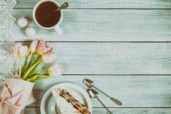 一个蛋糕用樱桃、茶和在白色木的桃红色郁金香 图库摄影