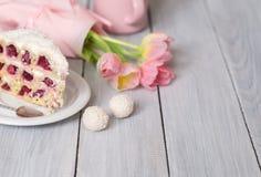 一个蛋糕用樱桃和桃红色郁金香在白色木桌上 免版税库存照片