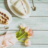 一个蛋糕用樱桃和桃红色郁金香在白色木桌上 库存照片