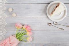 一个蛋糕用樱桃和桃红色郁金香在白色木桌上 免版税库存图片