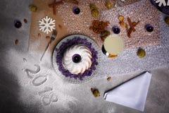 一个蛋糕的顶视图在2018新年标志旁边的 在桌背景的圣诞晚餐 圣诞节构成概念 免版税库存照片