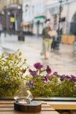 一个蜡烛的特写镜头在一个烛台的在一张木桌上,葡萄酒 雨天在城市 通过雨珠被看见的女孩  免版税库存图片
