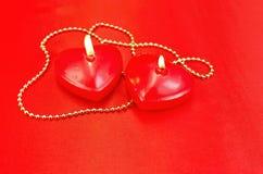 一个蜡烛的重点与一条项链的在红色丝绸 图库摄影