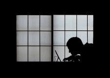 一个蠕动的计算机黑客的窗口剪影后弯成拱状在膝上型计算机在晚上 免版税库存照片