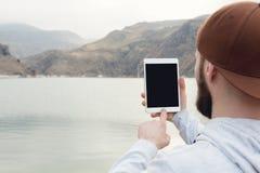 一个行家的特写镜头一个棕色盖帽的在他的手上露天拿着一台白色片剂个人计算机 一个有胡子的人看 免版税库存照片