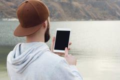 一个行家的特写镜头一个棕色盖帽的在他的手上露天拿着一台白色片剂个人计算机 一个有胡子的人看 库存照片