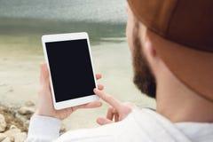 一个行家的特写镜头一个棕色盖帽的在他的手上露天拿着一台白色片剂个人计算机 一个有胡子的人看 免版税库存图片