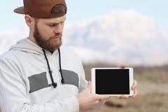 一个行家的特写镜头画象一个棕色盖帽的在他的手上露天拿着一台白色片剂个人计算机 一个有胡子的人神色 免版税库存图片
