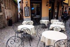 一个街道咖啡馆的看法与用桌布和桌的盖的椅子 免版税图库摄影