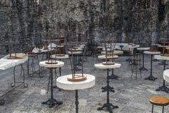 一个街道咖啡馆的表和椅子没有人的对一个粗砺的石墙 免版税库存照片