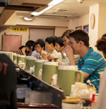 一个街道酒吧的内部与外国人的和日本的行 免版税库存照片