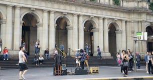 一个街道音乐家人表现H&M buildi他的显示的前面  免版税库存照片