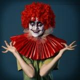 一个衣服可怕的小丑一顶红色假发的和红色vorotkike和绿色衬衣的疯狂的女孩在蓝色背景 万圣节 图库摄影