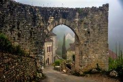 一个被成拱形的石门户的遗骸对中世纪法国村庄的 库存照片