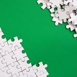 一个被折叠的白色七巧板的片段和堆以绿色表面为背景的蓬乱的难题元素 纹理 库存图片