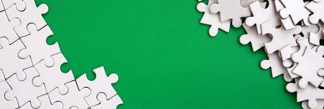 一个被折叠的白色七巧板的片段和堆以绿色表面为背景的蓬乱的难题元素 纹理 免版税图库摄影
