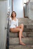 一个被放弃的大厦的台阶的美丽的女孩 免版税图库摄影