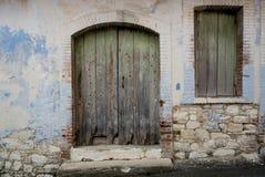 一个被放弃的房子的入口有绿色门和窗口的 免版税库存照片