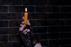 一个被点燃的蜡烛在女性手上 背景砖图象rastre墙壁 黑色手套 复制空间 题材假日万圣夜 库存照片