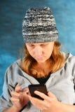 一个被编织的帽子的女孩有红色头发的在他的手上的拿着一个智能手机在蓝色背景在演播室 免版税库存图片
