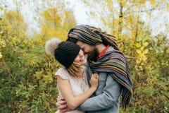 一个被编织的帽子的新娘有pom pom的,盖她的眼睛的帽子 一条五颜六色的围巾的新郎 婚姻的仪式户外 库存图片