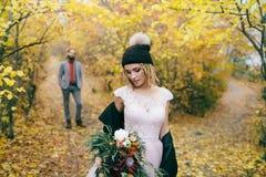 一个被编织的帽子的美丽的新娘有绒球的在被弄脏的新郎` s背景的秋天森林里摆在 婚姻 库存图片