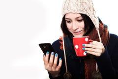 一个被编织的帽子的一个女孩微笑和拿着一个红色咖啡杯的和 库存照片