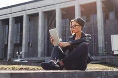 一个被编织的帽子的一个时兴地加工好的行家女孩在城市使用坐一种电子的片剂外面 库存照片