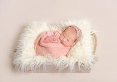 一个被编织的帽子的小睡的女婴 免版税库存照片