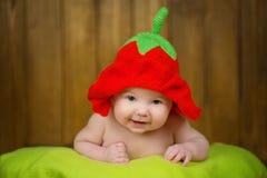 一个被编织的帽子草莓的美丽的女婴 免版税图库摄影