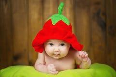 一个被编织的帽子草莓的美丽的女婴 库存图片