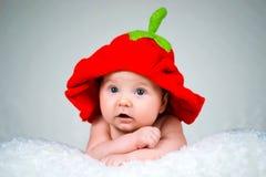 一个被编织的帽子草莓的美丽的女婴 库存照片