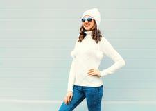 戴一个被编织的帽子,毛线衣的愉快的年轻微笑的妇女 库存照片