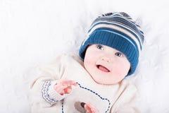 一个被编织的毛线衣和蓝色帽子的逗人喜爱的婴孩 免版税图库摄影