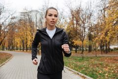 一个被集中的健身女孩的画象耳机跑步的 免版税图库摄影