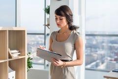 一个被集中的女性办公室助理、读书和文字新的企业想法,在她的藏品纸文件夹的画象 库存照片