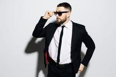 一个被集中的英俊的人的画象在衣服和手穿戴了在看起来的太阳镜去,当站立在灰色背景时 免版税库存图片