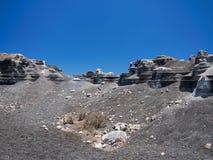 一个被雕刻的岩石由风力侵蚀雕刻了反对深蓝天背景  黑熔岩石渣 库存照片