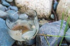 一个被风化的打破的玻璃瓶子在石头离开由河 库存图片