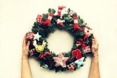 一个装饰的圣诞节花圈在妇女的手上 在空白背景 免版税图库摄影