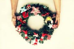 一个装饰的圣诞节花圈在妇女的手上 背景查出的白色 免版税库存照片