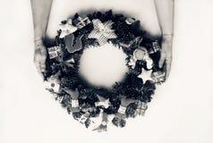 一个装饰的圣诞节花圈在妇女的手上 背景查出的白色 库存照片