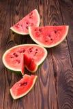 一个西瓜的一半在黑褐色木背景的 一个甜,新鲜,未加工和成熟西瓜的特写镜头 夏天果子 免版税库存照片