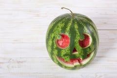 一个西瓜的微笑的面孔在万圣夜喜欢一个南瓜为 图库摄影