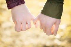 一个订婚的男人和妇女举行显示他们的爱的小指手指 图库摄影